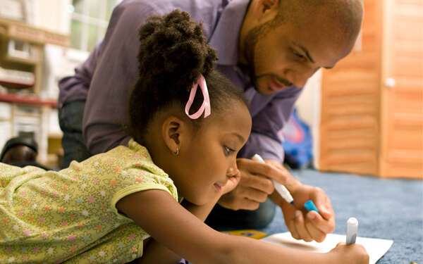a father teaching his daughter how to draw in their improved house